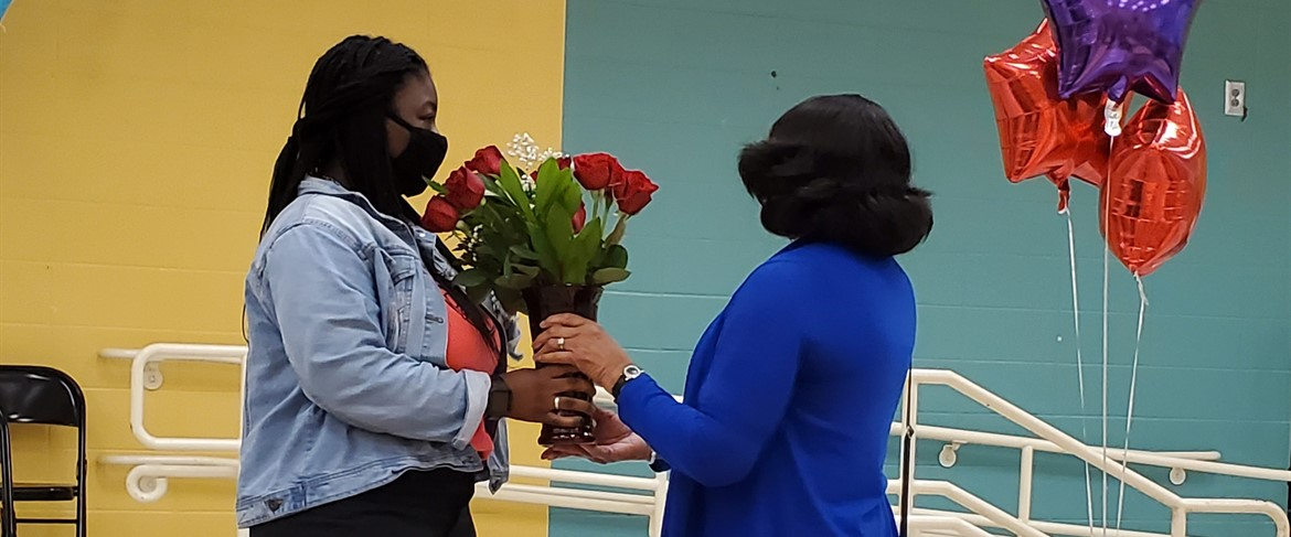 Ms. Booker presenting flowers to HES teacher of the year, Ms. Anderson.